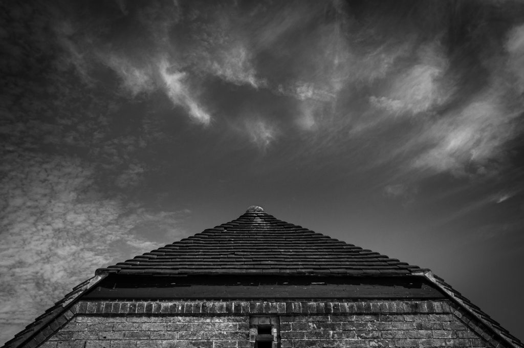 Black and white photo of a barn roof against a sky filled with clouds